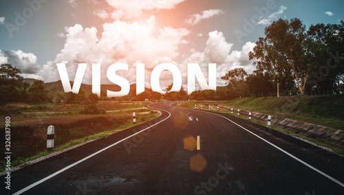 The word vision behind the tree of empty asphalt road at golden sunset and beautiful blue sky. Concept for vision.