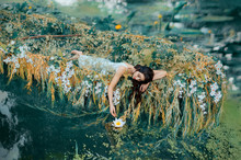 River Nymph In White Vintage Dress Lies In Boat Decorated Flowers Yellow Willow Branches, Enjoy Silence Relax. Long Flowing Dark Hair. Touches Hand Lily. Backdrop Autumn Orange Nature Green Water Lake