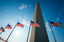 Backlit View Of American Flags Surrounding The Washington Monument In Bright Summer Sun In Washington, DC, USA