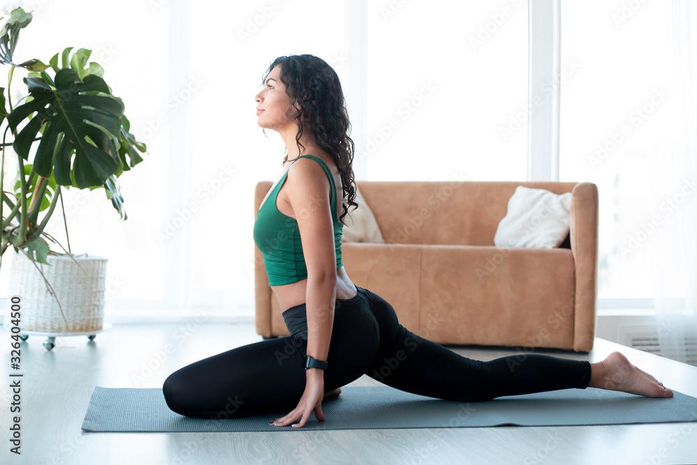 Fototapeta Attractive Latin woman doing yoga in living room. Pigeon pose