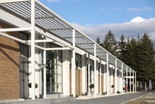 Yaslo, Poland - 7 8 2019: Design Of A Modern Building Of A Sports Complex. A Perspective View Of The Facade Of A House With An Orc And Large Glass Windows. Landscaping With Green Spaces. Feng Shui