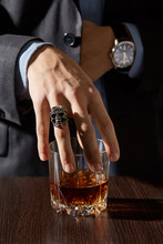 Cropped Shot Of A Man In A Gray Formal Suit, A Blue Shirt And With A Classic Watch And A Silver Skull Ring On The Finger. The Man Is Touching A Whiskey Glass With An Amber Drink On The Brown Table.