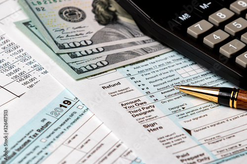 Fototapeta 1040 income tax return form 2019 with money, calculator, and pen. Focus on refund. Concept of filing taxes, payment, refund and April 15, 2020 tax deadline obraz