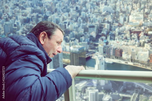 Photo A man experiences acrophobia symptoms being on the viewing platform above a big city