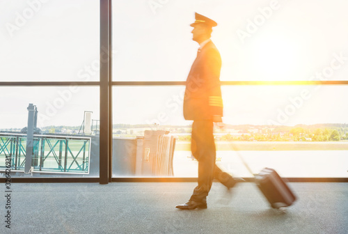 Valokuva Portrait of mature pilot walking in airport with yellow lens flare