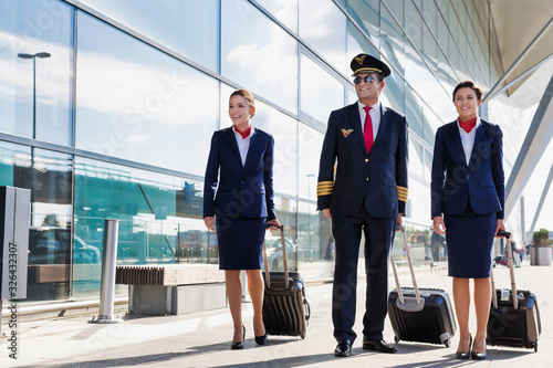 Mature pilot with young beautiful flight attendants walking in airport Canvas Print