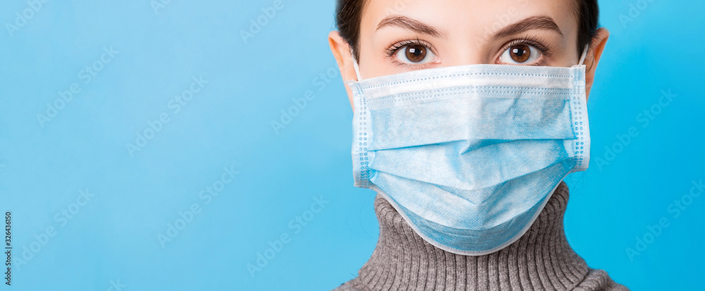 Fototapeta Portrait of young woman wearing medical mask at blue background. Protect your health. Coronavirus concept