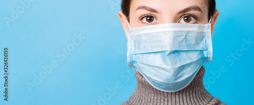 Tela Portrait of young woman wearing medical mask at blue background