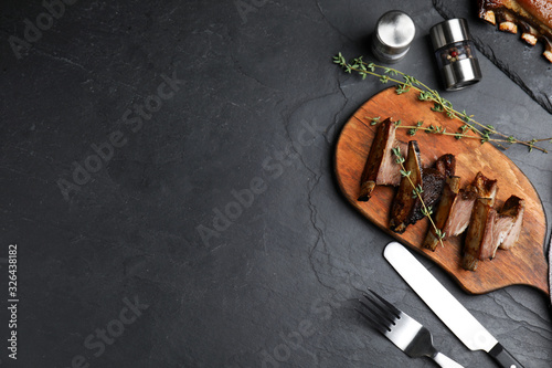 Photo Delicious roasted ribs served on black table, flat lay