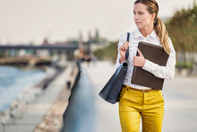 Portrait Of Young Attractive Businesswoman Walking While Holding Document
