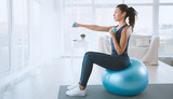 Young woman with gym ball and dumbbells at home, blank space