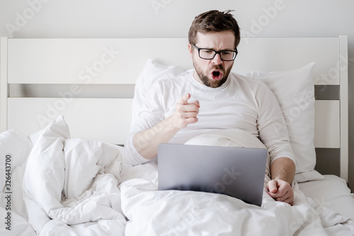 Fényképezés Dissatisfied, angry man communicates remotely through a video call from a laptop, sitting in bed