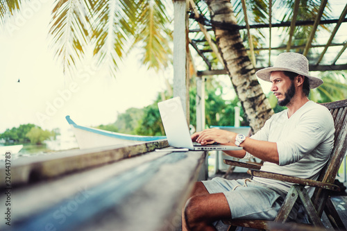 Obraz Technology and travel. Working outdoors. Freelance concept. Bearded young man using laptop in cafe on tropical beach. - fototapety do salonu