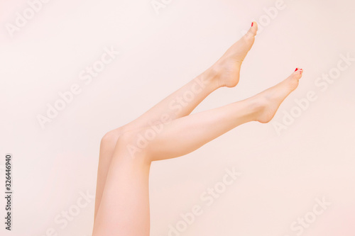 Photo Female bare legs raise, On a beige background