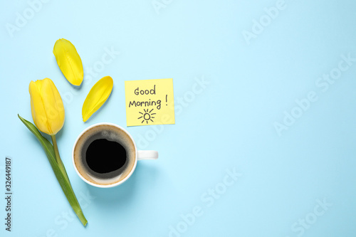 Delicious coffee, tulip and card with GOOD MORNING wish on light blue background, flat lay. Space for text