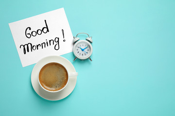Delicious coffee, alarm clock and card with GOOD MORNING wish on light blue background, flat lay. Space for text