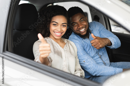 mata magnetyczna Happy Couple Gesturing Thumbs-Up Sitting In Car In Dealership Store