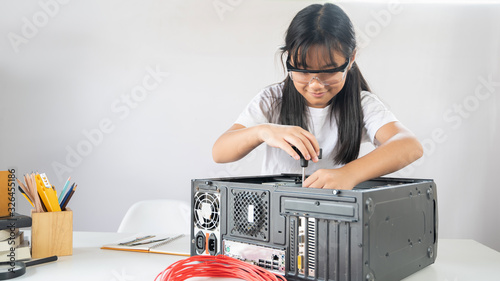 Valokuvatapetti Photo of young adorable girl fixing/installing a computer hardware at the modern white working desk
