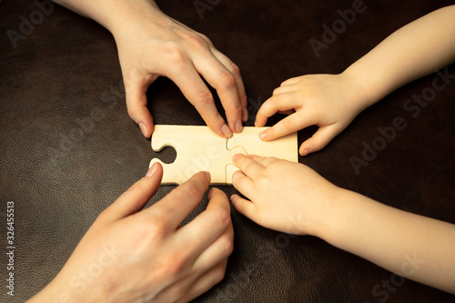 Obraz Collecting pazzles, building future. Close up shot of female and kid's hands doing different things together. Family, home, education, childhood, charity concept. Mother and son or daughter, wealth. - fototapety do salonu