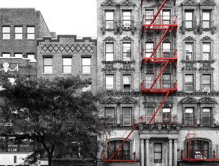 Panel Szklany Nowy York Red fire escape on the exterior of an old building in black and white - Manhattan, New York City