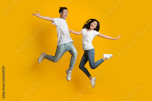 Emotional asian couple jumping over yellow background