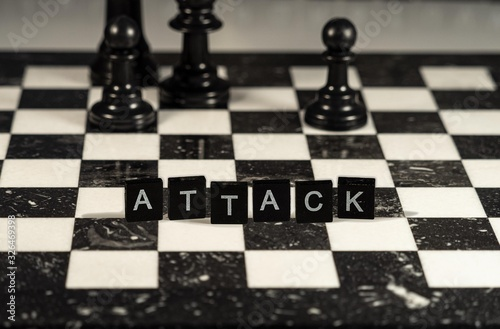 The concept of Attack represented by black and white letter tiles on a marble ch Wallpaper Mural