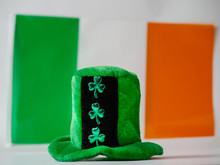 Green Hat With Shamrock, Irish National Flag In The Background. Saint Patrick Day Celebration.