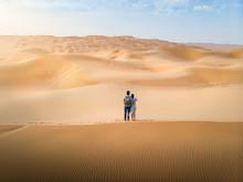 Couple Enjoying Desert Scenery At Sunset Aerial View
