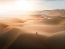 Woman Walking On The Desert Sa...
