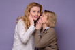 Two beautiful caucasian mature women telling secret on a colored background.