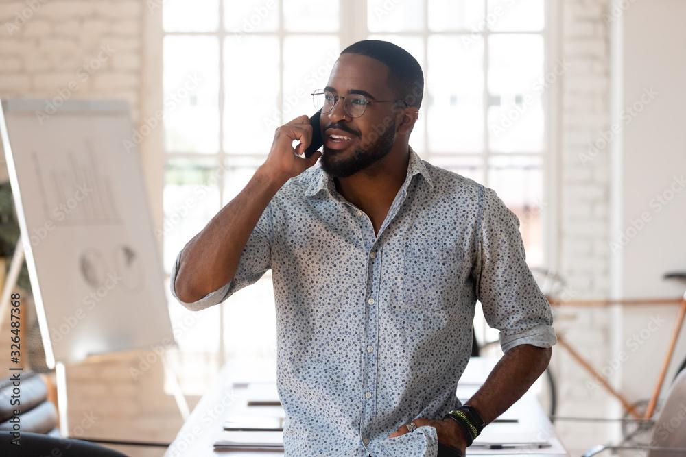 Fototapeta African businessman talking on phone inside of modern office