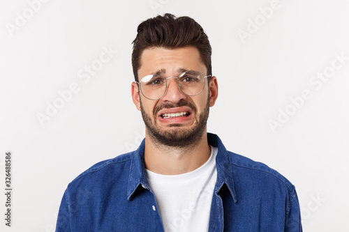Fotografie, Tablou Close up portrait of disappointed stressed bearded young man in shirt over white background