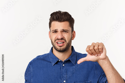 Vászonkép Close up portrait of disappointed stressed bearded young man in shirt over white background