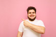 Happy young man with overweight and beard isolated on a pink background, looks into the camera and smiles, points his finger away at copy space. Fat guy in a white shirt shows an empty space