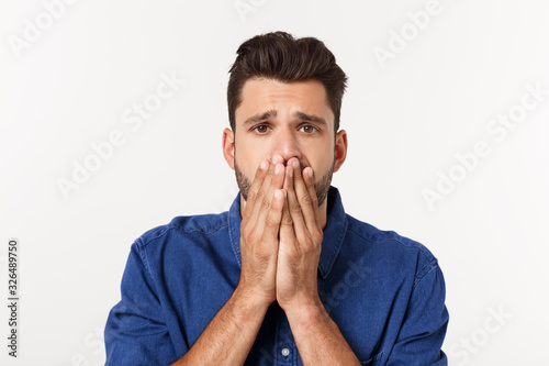 Fényképezés Close up portrait of disappointed stressed bearded young man in shirt over white background