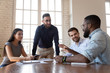 Middle eastern ethnicity employee listens african colleague during group meeting
