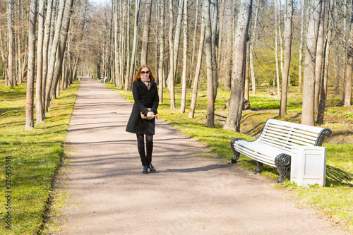 Photo Red-haired lass takes a walk by allay in Oranienbaum park