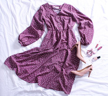 Purple Polka Dot Midi Dress, Beige High Heel Shoes, Nail Polish, Lip Gloss And Accessories On Bed On White Sheet. Women's Stylish Spring Outfit. Trendy Clothes Collage. Flat Lay, Top View.