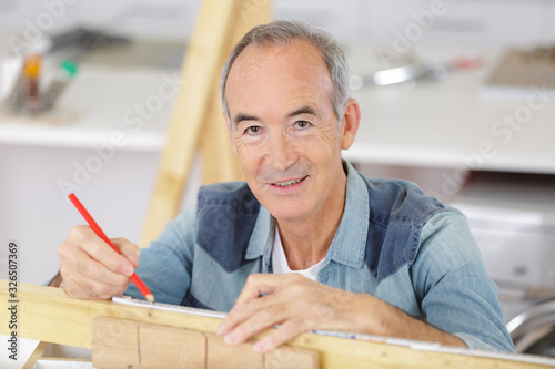 senior man measuring wood on saw Wallpaper Mural