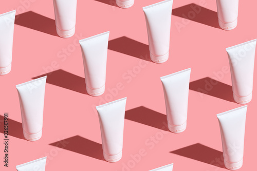 White cream tubes on light pink table Fototapete
