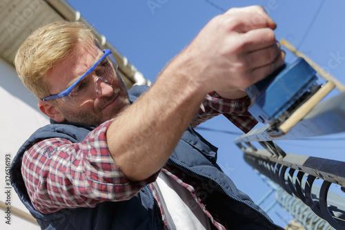 Photo a man sanding outdoor handrail