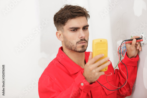 Photo an electrician measuring the voltage