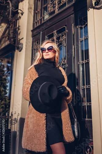 Portrait of stylish young woman in coat sunglasses with purse outdoors. Spring fashion female clothes accessories. Wall mural
