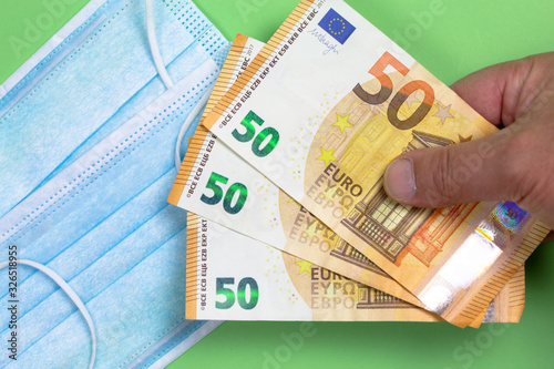 Fotomural Protective surgical mask with several 50 euro notes held by a man's hand to illu