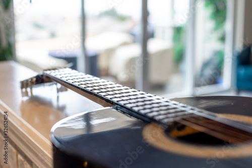 Fototapeta Selective focus on the neck, frets and strings of an acoustic guitar with blurre