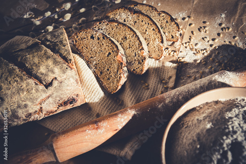Obraz dark sliced bread with wheat and flour on the table. Sliced rye bread on a close-up on the table and scattered grains of wheat around Brown bread and grains look beautiful. Put on a wooden table. - fototapety do salonu