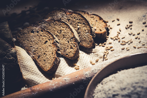 dark sliced bread with wheat and flour on the table Canvas-taulu