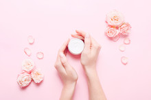 Open Jar With Cream For Skin Care And Roses In Female Hands On Pink Background.