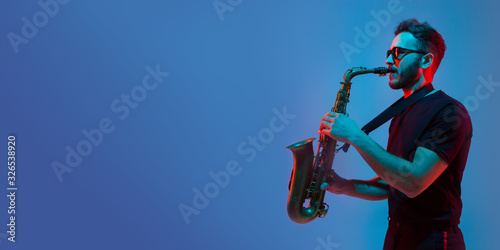 Photo Young caucasian jazz musician playing the saxophone on gradient blue-purple studio background in neon light
