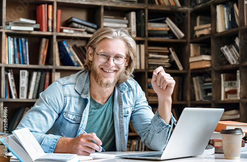 Carta da parati Portrait young bearded male college student glasses sit at home library desk handwrite notebook hold pen make notes from textbook laptop prepare project study online exam test web e education concept